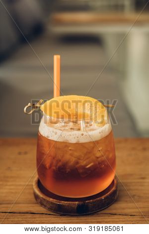 The Glass Of Peach Ice Tea On Wooden Table In Coffee Shop.iced Tea Cocktail, Cold Drink Or Lemonade