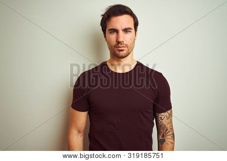 Young handsome man with tattoo wearing purple casual t-shirt over isolated white background Relaxed with serious expression on face. Simple and natural looking at the camera.