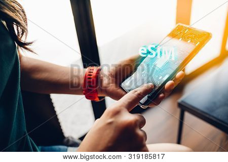 Close Up Of Woman Using A Phone With Esim Technology. Mobile Device With A Chip On A Circuit Board A