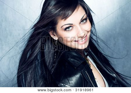 smiling blue eyes young woman with healthy and shiny long hair in black leather jacket, studio shot
