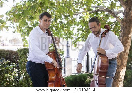 Street Musicians In Big City Playing On Instrument