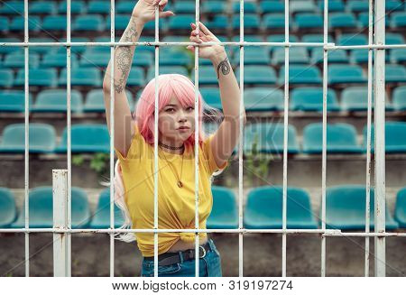 Eccentric Pink Haired Asian Woman Holding On Fence Looking At Camera