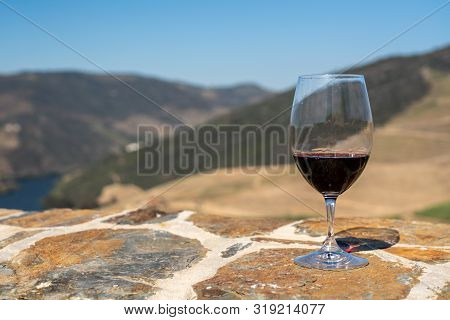 Glass Of Red Wine Or Port For Tasting Above The Hillsides Of The Douro Valley In Portugal