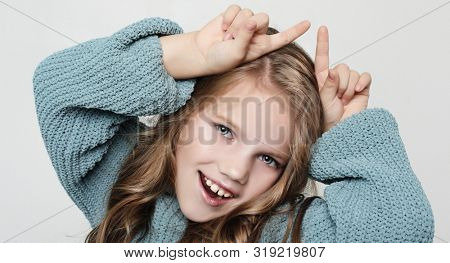 Portrait of positive happy child with curly hair, holding index fingers above head, mimicking horns and smiling