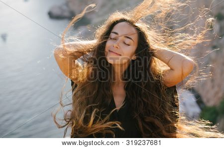 Young Beautiful Happy Woman With Long Curly Hair Posing On A Top Of The Mountain With Sea View.