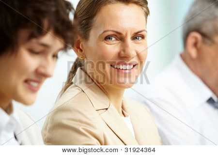 Smiling business woman looking at camera among her partners