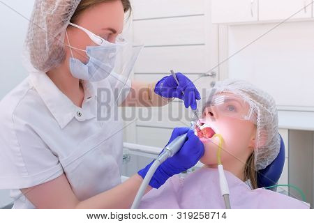 Dentist Cleaning Brushing And Polishing Womans Teeth Uses Drill In Dentistry. Dental Hygienist Make