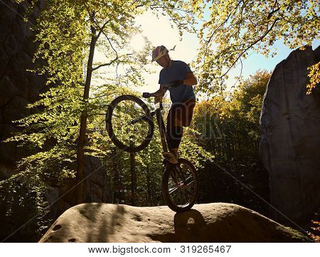 Professional sportsman bicyclist balancing on back wheel on trial bicycle, male cyclist making acrobatic stunt on big boulder in the forest on sunny day. Concept of extreme sport active lifestyle poster