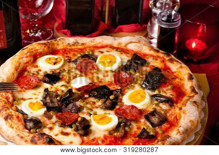 Italian Pizza With Fried Eggplants, Hot Salami, Eggs And Green Peas