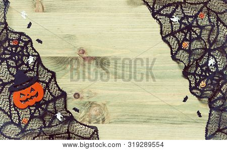 Halloween background. Spider web, cobweb lace and smiling jack decorations as the symbols of Halloween on the wooden background, vintage tones applied