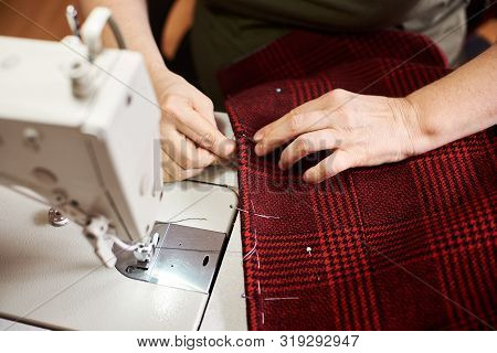 Top View Of Preparing Process Before Sewing Plaid Red Fabric. Clothier Female Hands Fixing, Fitting