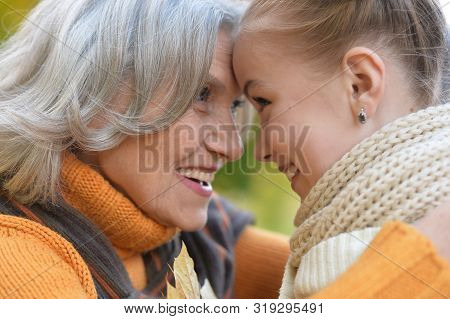 Close Up Portrait Of Granny And Granddaughter Posing Outdoors