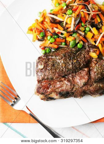 Grilled steak with vegetables salad on the white plate. Healthy nutrition.