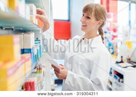 Smiling pharmacist or Chemist woman sorting drugs in shelves in her pharmacy
