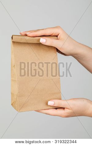 Close - Up Of A Woman Holding A Brown Empty Paper Bag Isolated On A Grey Background. Service Deliver