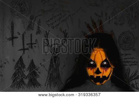 Spooky Bloody Pumpkin Face Of A Halloween Creature On Dark Background With Occult Symbols. Close-up