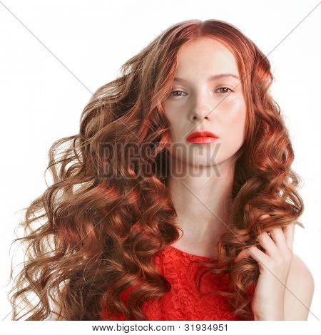 Giovane e bella donna con i capelli lunghi ricci a luce rossa