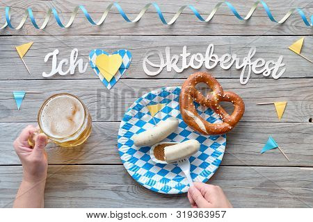 Oktoberfest, Traditional Festival Food: White Sausages, Pretzel And Beer. Flat Lay With Hands And Fe