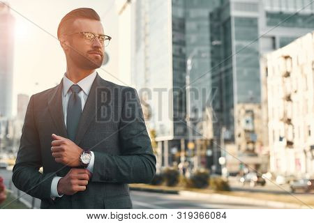 Portrait Of Young And Handsome Bearded Man In Full Suit Adjusting His Sleeve And Looking Away While