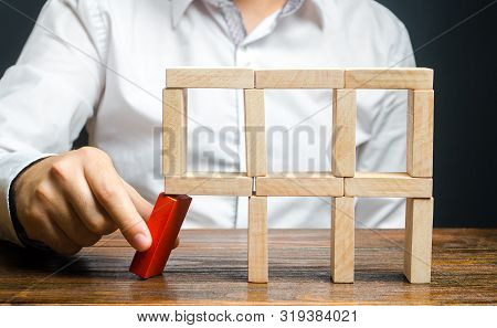 The Man Removes The Red Structural Element, Which Will Collapse. Destruction Of A Complex Structure