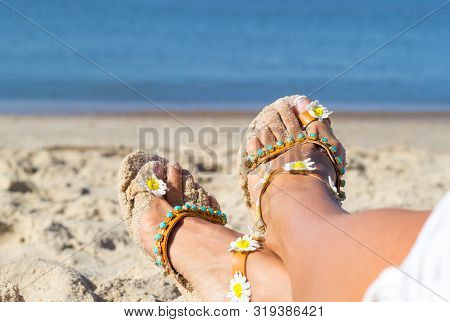 Holidays At Sea Background With Copy Space. Female Feet Shod In Sandals Lay On Golden Sand Near Seas