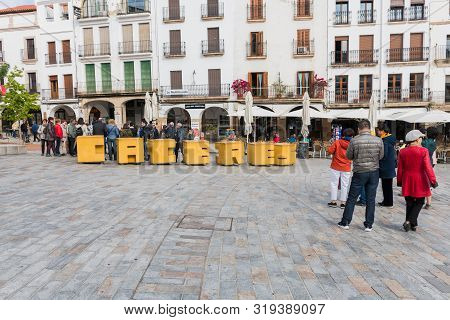 Caceres, Extremadura, Spain - April 25, 2019: A Group Of Asian Tourists Take Photographs Next To The