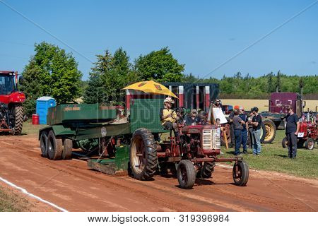 Dundas, Prince Edward Island / Canada - August, 25, 2019: Competitors with their tractors hauling a weighted sled in the annual tractor pull competiton at the PEI Plowing Match and Agricultural Fair,