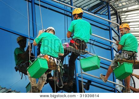 Unidentified workers washing a windows facade