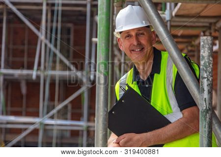 Male builder foreman, construction worker, surveyor or site manager holding a clipboard, wearing a white hard hat and hi vis vest and smiling