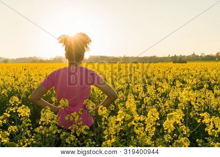 Outdoor beautiful rear view in golden evening sunshine of fit healthy and happy mixed race African American girl teenager female young woman relaxing hands on hips in field of yellow flowers at sunset