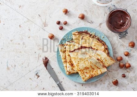 Homemade crepes, tasty thin pancakes with chocolate and nuts.