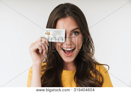 Image of gorgeous brunette woman wearing casual clothes smiling and holding credit card isolated over white background