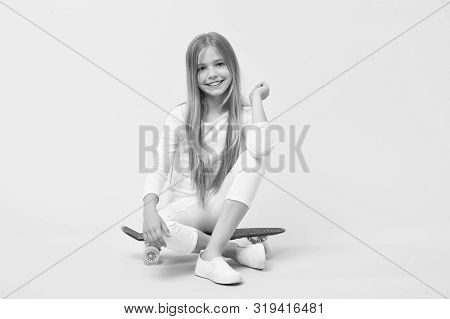 Enjoying Vibes On Penny Board. Cute Little Child Sitting On Penny Board Deck On Pink Background. Ado