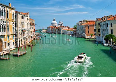 View of Venice Grand Canal with boats and Santa Maria della Salute church in the day from Ponte dell'Accademia bridge. Venice, Italy