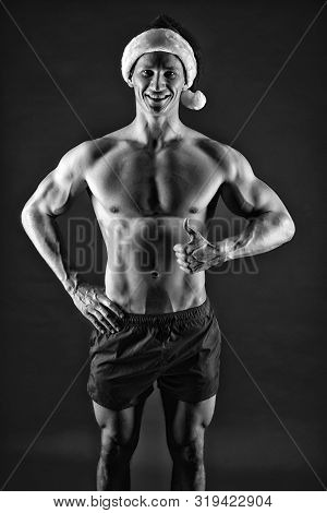 Athlete man wear santa hat and red shorts. Sexy athletic macho in santa claus hat. If you were very bad girl. Macho sexy muscular torso posing confidently. Santa claus comes not only to good girls. poster
