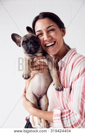 Studio Portrait Of Smiling Young Woman Holding Affectionate Pet French Bulldog Puppy poster