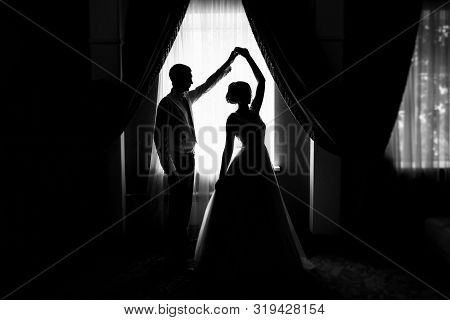 Bride And Groom At The Window. Silhouette Of The Bride And Groom At The Window. Silhouette Of Newlyw