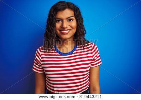 Transsexual transgender woman wearing stiped t-shirt over isolated blue background with a happy and cool smile on face. Lucky person.