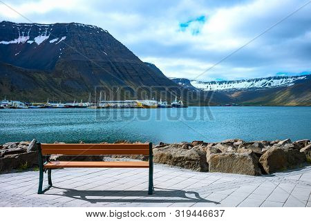 Isafjordur, Iceland, A Bench On The Edge Of The Bay With The Fishermen Harbor In The Background