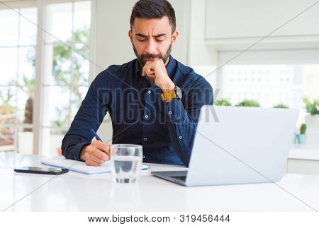 Handsome hispanic man working using computer and writing on a paper serious face thinking about question, very confused idea
