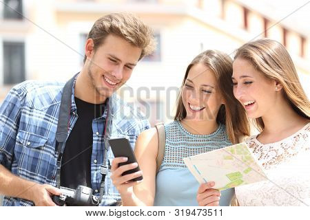 Three Happy Tourists Traveling Checking Smart Phone Gps And Map In The Street On Summer Vacation