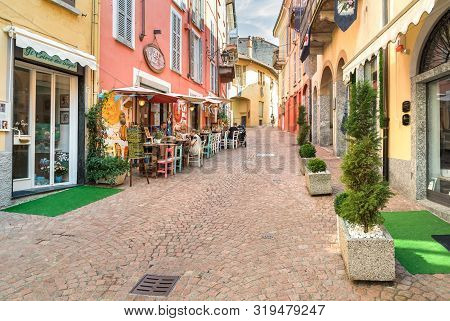 People Enjoying The Typical Italian Street Bars And Restaurants In The Historic Center Of Luino, Ita