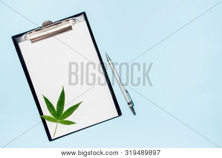 Top View Of Blank Paper For Writing Doctor Prescription. Marijuana Leaf With Medical Pills On Blue B