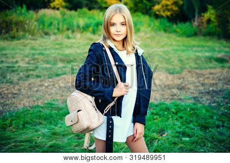 A beautiful young girl with a backpack in the coutryside. Autumn fashion, beauty.