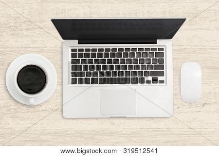 Laptop Computer And A Cup Of Coffee On Wooden Table.