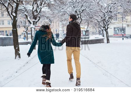 Young Loving Couple Dressed In Plaid Scarves Walk, Run And Laugh At The Old City In Winter. Man And
