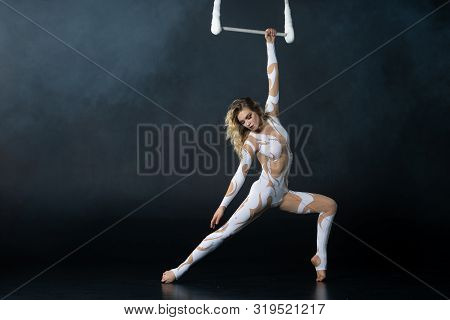 A Young Girl Performs The Acrobatic Elements In The Air Trapeze. Studio Shooting Performances On A B
