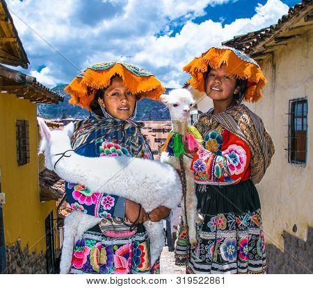 Cusco, Peru - Jan 9, 2019: Unidentified girls traditional dressed with lamas on the street of Cusco, Peru