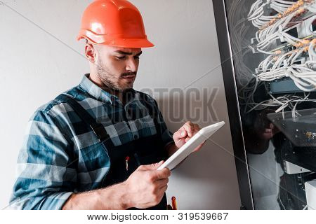handsome workman using digital tablet near cables and wires poster