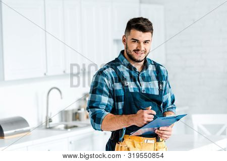 happy bearded workman holding clipboard and looking at camera in kitchen poster